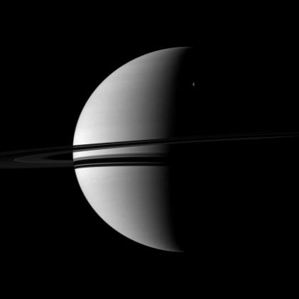 Saturn in crescent and its moon Rhea